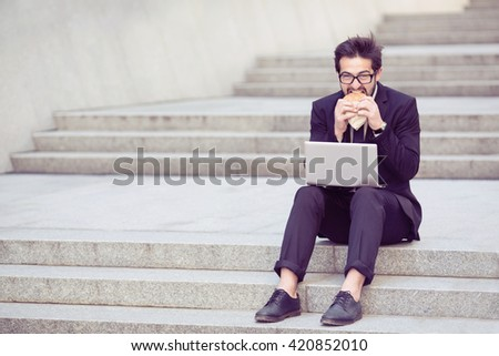 Toned picture of businessman eating hamburger during his work in city cente as freelancer. Handsome man in business suit working on laptop computer. - stock photo