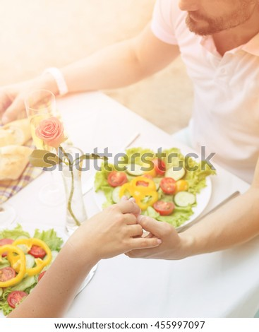 Toned picture of couple of man and woman holding hands and resting in restaurant or cafe by sea. Beautiful mature couple in love having date.