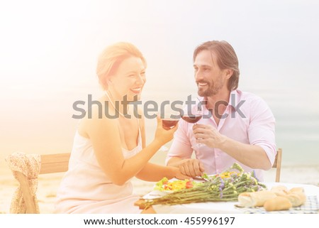 Toned picture of happy couple spending free time all together in restaurant or cafe. Handsome man and beautiful woman having lunch with red wine. People laughing, hugging and kissing.
