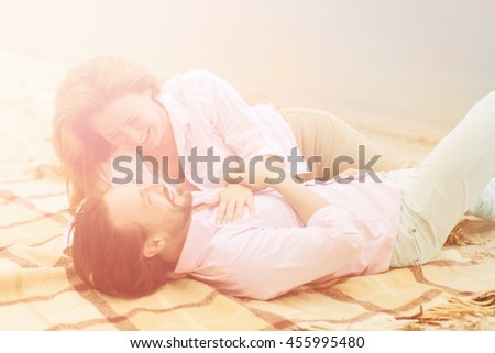 Toned picture of happy middle-aged couple enjoying their summer holidays all together near by sea. Beautiful people smiling and looking at each other. - stock photo