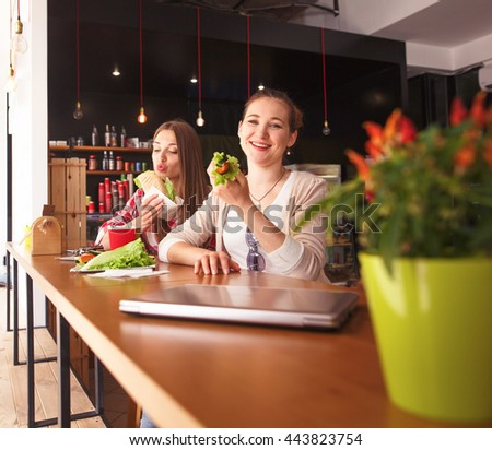 Toned picture of pretty ladies sitting in cafe. Happy girls eating sandwiches or snacks during break. - stock photo