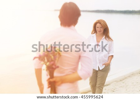 Toned picture of romantic couple walking on sandy beach. Handsome man hiding bouquet of flowers for his wife. Beautiful red-haired woman reaching to him with hands in pockets.