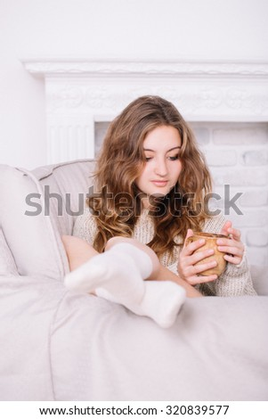 Toned portrait of a beautiful and sexy young adult attractive dreaming woman in beige sweater and vanilla socks sitting on the beige armchair with cup of coffee in her hand in the white room.