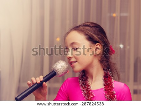 Toned portrait of Beautiful girl singing into a microphone - stock photo
