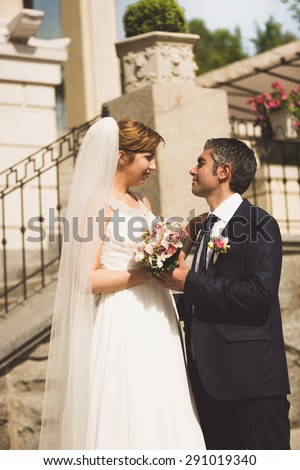 Toned portrait of bride and groom looking at each other on ancient street