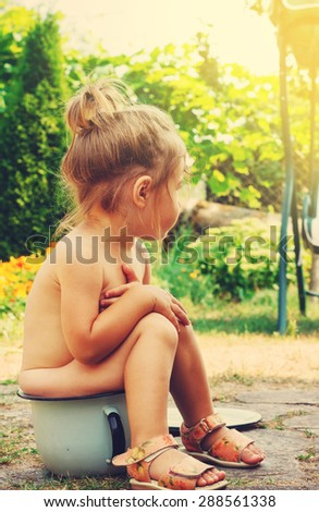 Toned portrait of Cute Happy toddler sitting on potty outdoor - stock photo