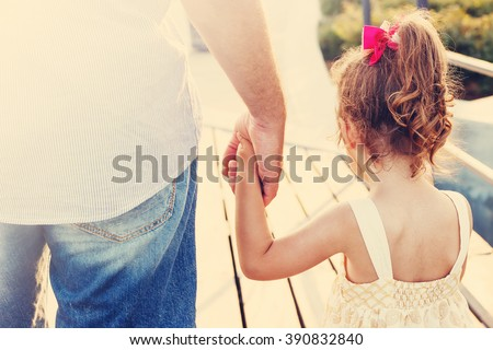 Toned portrait of Father and daughter holding hand in hand at sunset - stock photo