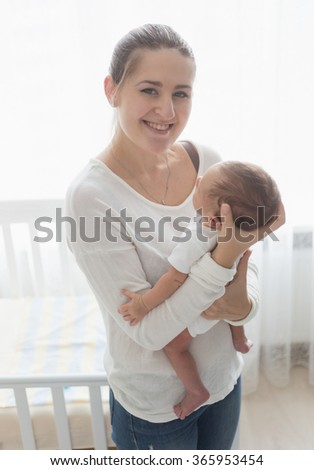 Toned portrait of happy smiling mother posing with her little baby - stock photo