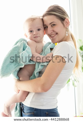 Toned portrait of happy young mother hugging her baby boy covered in blue towel after bathing - stock photo