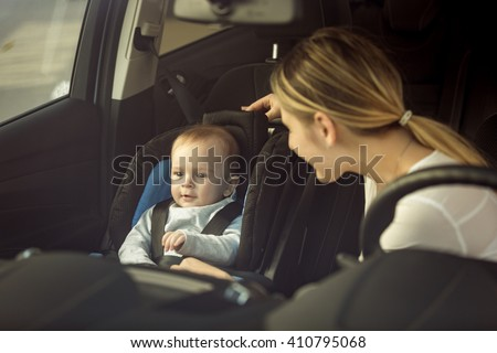 Toned portrait of mother and baby boy sitting in car on front seats - stock photo