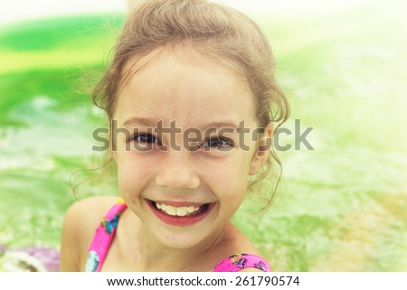 Toned portrait of Pretty little girl swimming in outdoor pool