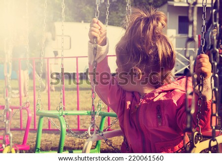 toned portrait of Sad little girl sitting on swing in a park, looks for her mum - stock photo