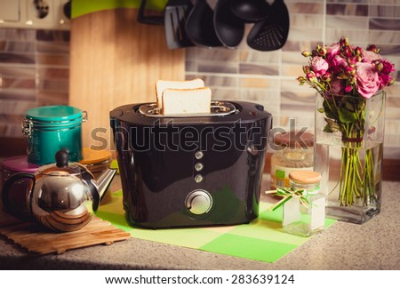 Toned shot of toaster with fresh brad on beautiful decorated kitchen - stock photo