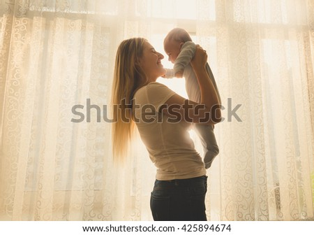 Toned silhouette portrait of happy mother and little baby posing against big window - stock photo
