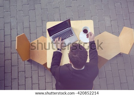 Toned top view picture of businessman using laptop computer and drinking cup of coffee in cafe or restaurant. Freelance concept. - stock photo