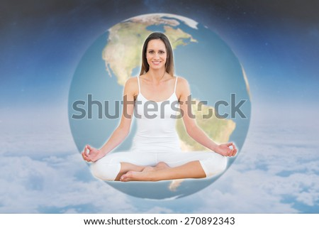 Toned woman in lotus pose at fitness studio against white clouds under blue sky