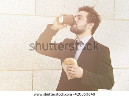 Tonedpicture of handsome businessman eating junk food and drinking tea or coffee on to go to work. Freelancer man in hurry having snack. - stock photo