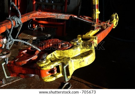 Tong used for making up and breaking out connections on oil rigs - stock photo