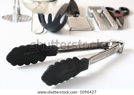 Tongs and other kitchen utensils in the background. - stock photo