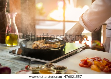 Tongs touch fried meat. Cut onion and tomatoes. How to prepare juicy pork. Dish for true gourmets.