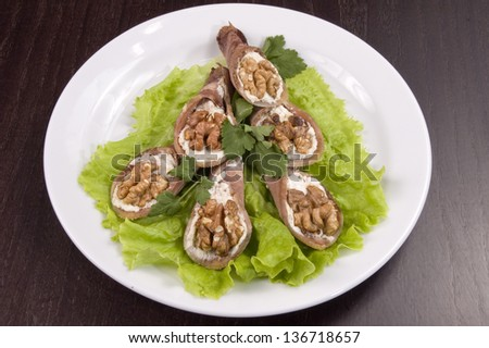 Tongue stuffed with a nut on a white plate.