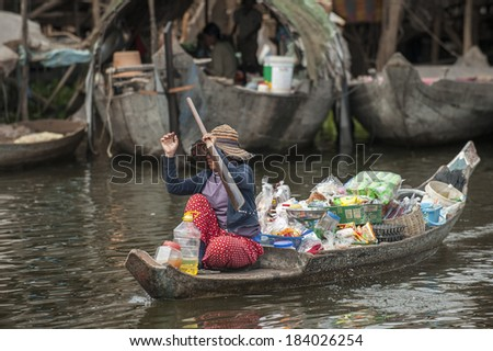 TONLE SAP, CAMBODIA - DECEMBER 24, 2011: Unidentified Cambodian woman rowing her sampan and selling goods in Tonle Sap water village, near Siam Reap,Cambodia on December 24, 2011