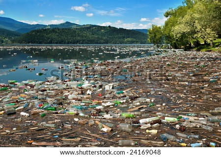 tons of plastic bottles and other waste floating on beautiful lake - stock photo