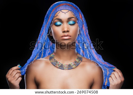 Too beautiful to be true. Beautiful African woman covering head by scarf and keeping eyes closed while standing against black background - stock photo