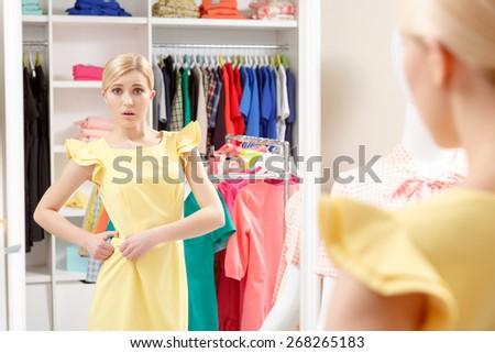Too loose. Young girl looking with disappointment into the mirror fitting her dress on the belt