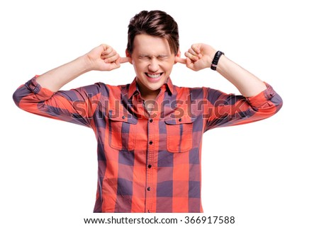 Too loud! Handsome young man in plaid shirt closing his ears with fingers refusing to listen to something. Isolated on white. - stock photo