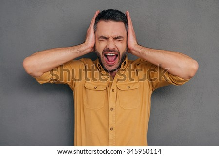 Too loud sound! Furious mature man covering ears with hands and shouting while standing against grey background - stock photo