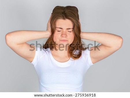Too loud sound. Teenage girl covering ears with hands and keeping eyes closed - stock photo