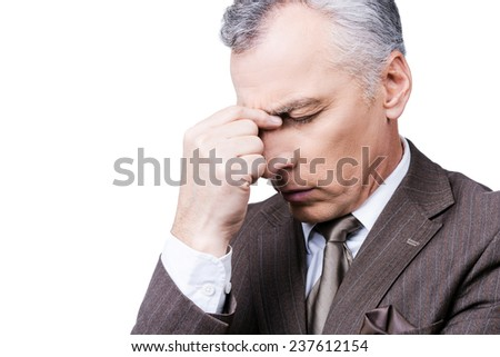 Too much problems. Frustrated mature man in formalwear touching head with fingers and keeping eyes closed while standing against white background - stock photo