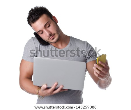 Too much technology. Young man using two mobile phones and one laptop computer, isolated on white