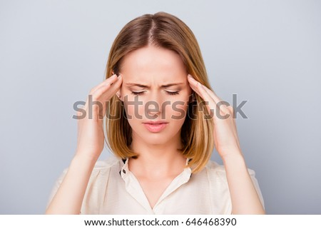 Too much work! Close up of depressed young blond woman with terrible headache touching temples with fingers on pure light background