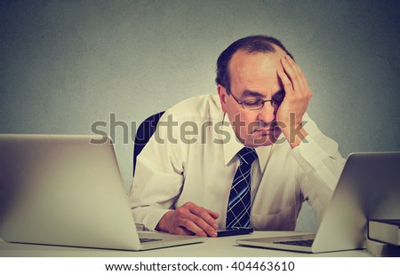 Too much work tired sleepy middle aged man sitting at his desk with books in front of two laptop computers isolated on grey wall office background. Busy schedule in college workplace sleep deprivation - stock photo