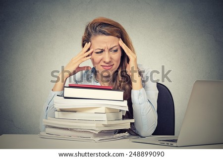 Too much work tired stressed young woman sitting at her desk with books in front laptop computer isolated grey wall office background. Busy college schedule burnout workplace sleep deprivation concept - stock photo