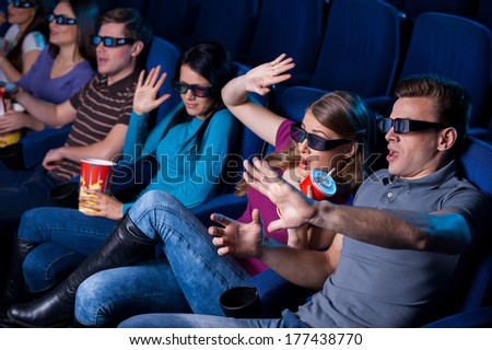 Too realistic movie. Top view of people in three-dimensional glasses watching movie and gesturing while sitting at the cinema  - stock photo