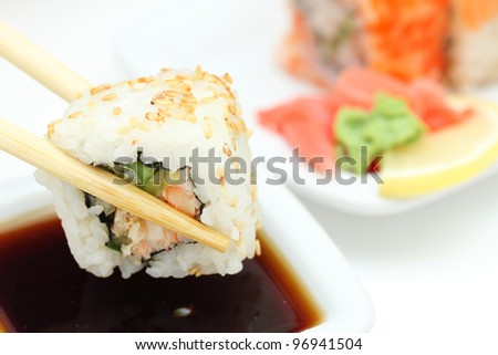 Took a sushi roll by the chopsticks , closeup - stock photo