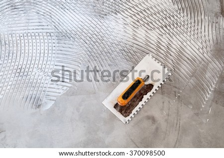 Tool and floor texture or abstract background . This texture of white adhesive latex on concrete floor created by worker's hand tool.  - stock photo