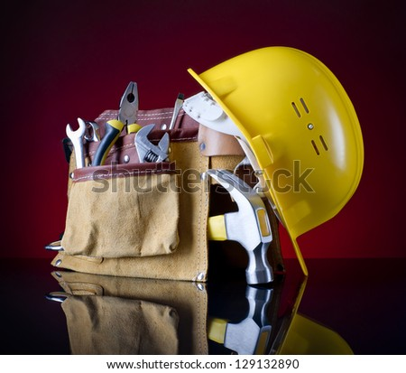 tool belt, hammer and a yellow helmet on a red glass background - stock photo