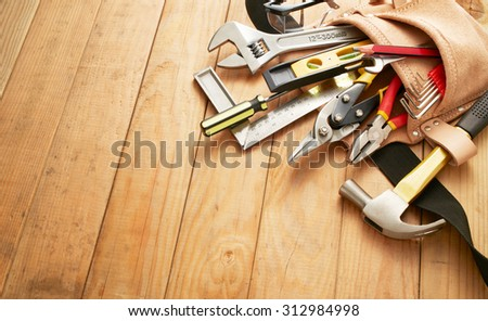 tool belt with tools on wood planks with copy space - stock photo
