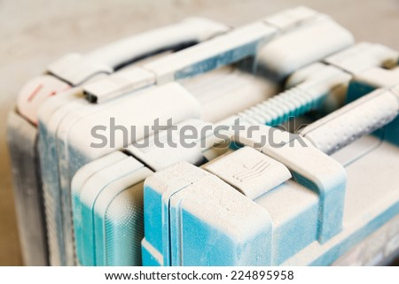 tool boxes under a layer dust on the table - stock photo