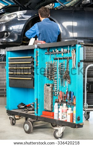 Tool cart with male mechanic repairing car in background at garage - stock photo