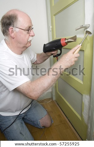 Tool man using paint remover - stock photo