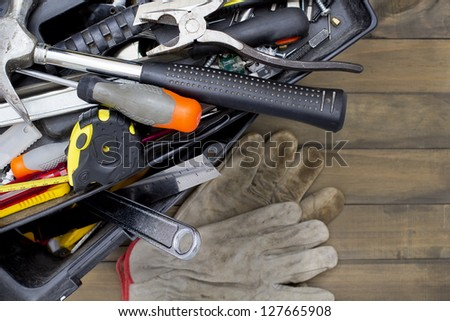 Toolbox with various tools on a wooden surface. - stock photo