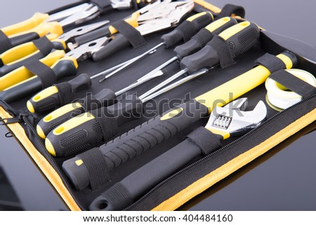 Toolkit black and yellow on black table - stock photo