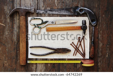 tools and paper against wooden wall - stock photo