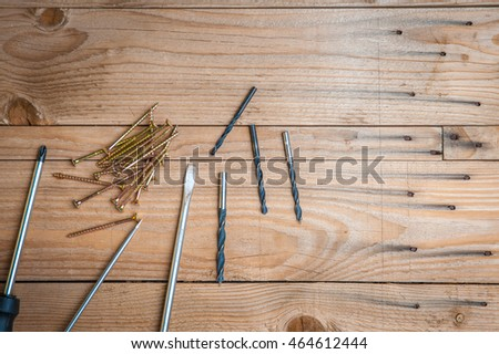 Tools and screws on a wooden background