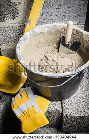 Tools for bricklayer bucket with a solution and a trowel, close-up - stock photo